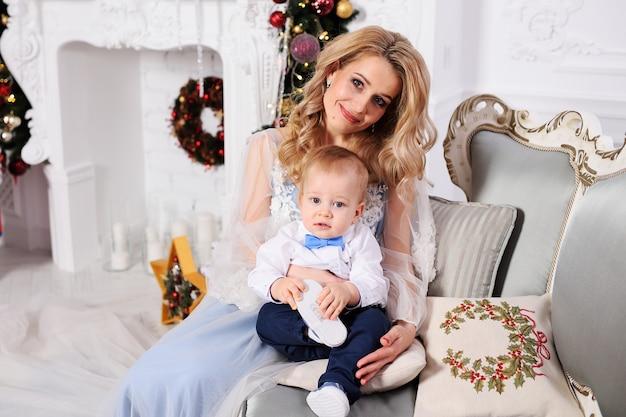Petit garçon avec sa mère en habits élégants assis