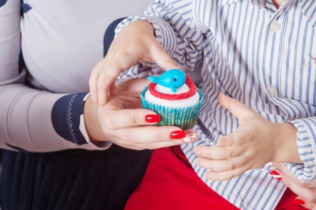 Petit garçon et sa mère tenant le gâteau d'anniversaire