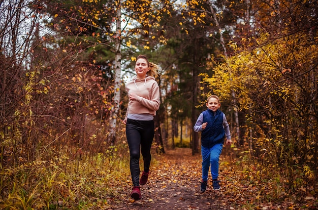 Petit garçon et sa soeur courir dans la forêt d'automne