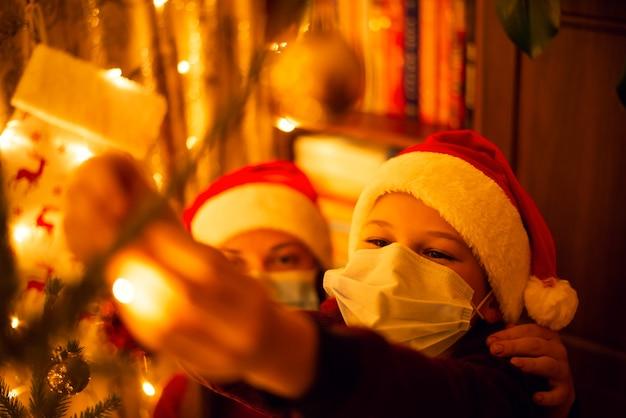 Petit garçon et sa soeur dans des masques médicaux de protection et des chapeaux de père noël rouge décoration arbre de noël