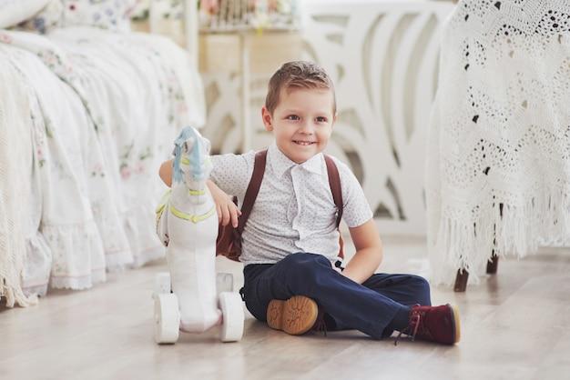 Petit garçon avec un sac à dos est assis dans la chambre des enfants et joue avec des jouets. pour la première fois à l'école. enfance heureuse