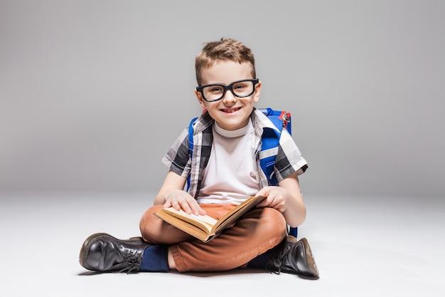Petit garçon avec sac à dos livre de lecture en posture de yoga