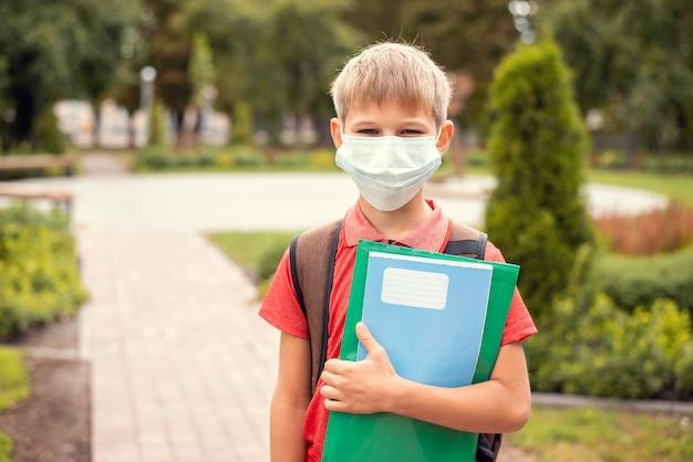 Petit garçon avec sac à dos et masque de protection dans le parc sur le chemin de l'école