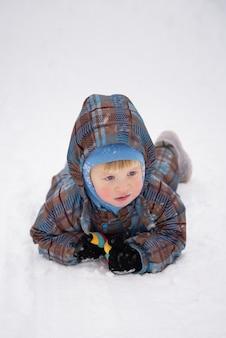Petit garçon en salopette est couché dans la neige. activités de la saison d'hiver