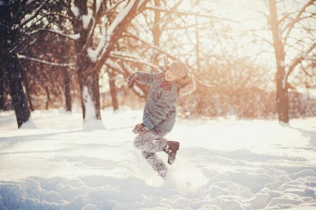 Petit garçon sautant dans le parc d'hiver
