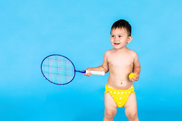 Petit garçon sautant et jouant au badminton sur mur bleu