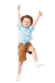 Petit garçon sautant et s'amusant isolé sur blanc