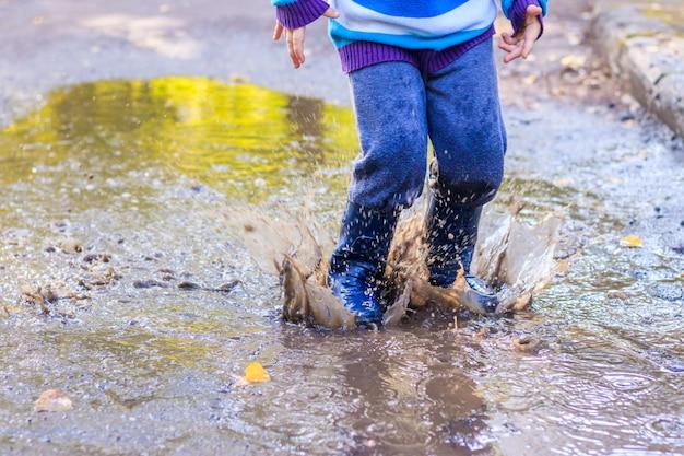 Un petit garçon saute dans une flaque d'eau.