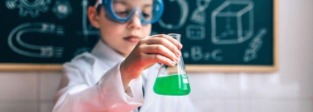 Petit garçon scientifique avec des lunettes tenant une fiole avec un liquide vert chimique contre un tableau noir dessiné