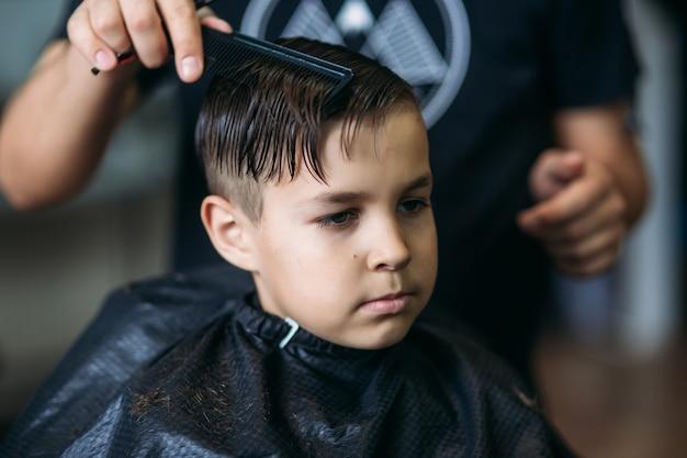 Petit garçon se coupe de cheveux par barber tout en étant assis sur une chaise au salon de coiffure.