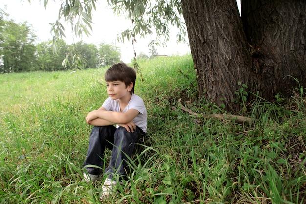 Petit garçon se demandant sous l'arbre