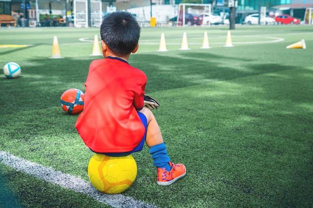 Petit garçon se détend dans le terrain d'entraînement de football