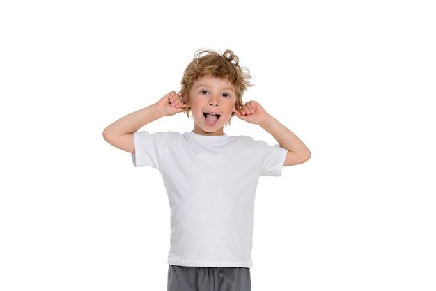 Petit garçon se lève et montre sa langue, il est de bonne humeur pour s'amuser.
