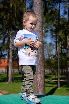 Un petit garçon se promène sur le territoire de l'aire de jeux à l'extérieur par beau temps