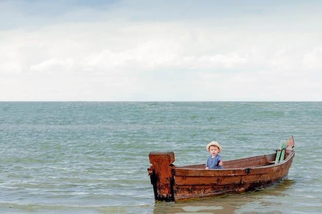 Petit garçon se repose dans un bateau sur le lac