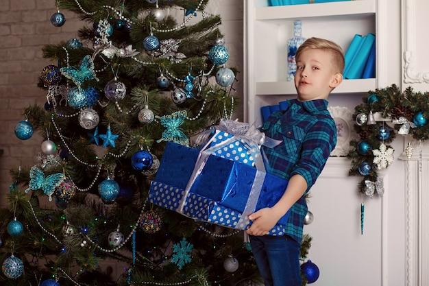 Petit garçon se tient près de l'arbre de noël détient des cadeaux de noël.