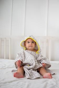 Un petit garçon sérieux est assis dans une serviette de bain à capuchon sur un lit blanc et regarde ailleurs. orientation verticale