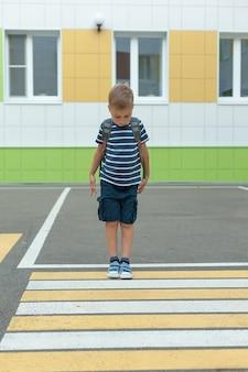 Un petit garçon seul traverse la route à un passage pour piétons