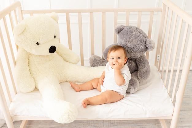 Un petit garçon de six mois est assis dans son berceau avec de gros ours en peluche dans une pièce lumineuse