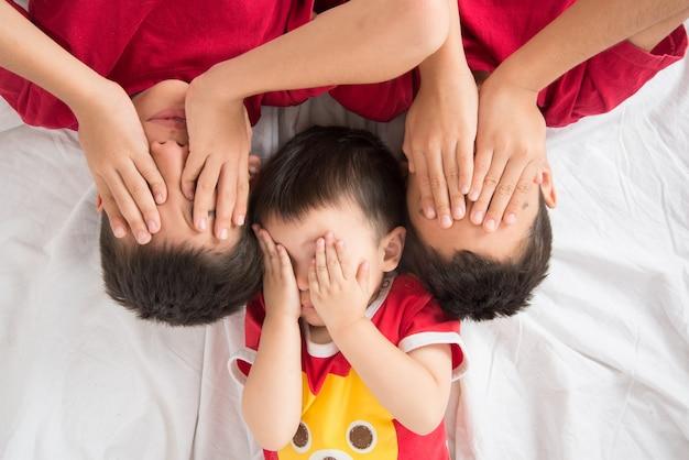 Petit garçon de soeur allongé sur le sol regarde la caméra aime et heureux