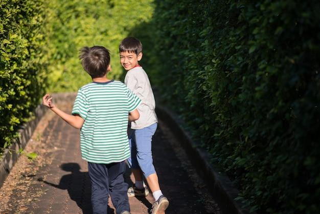Petit garçon de soeur marchons ensemble dans un parc public vert