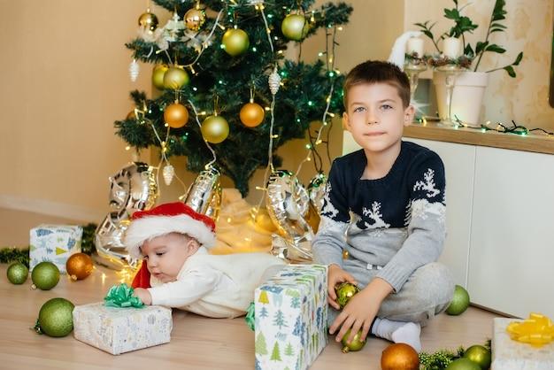 Petit garçon et son frère jouent avec des cadeaux sous un arbre de noël festif