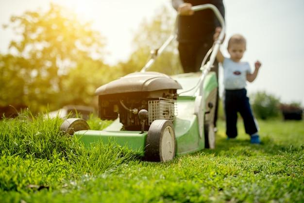 Petit garçon et son grand-père tondant l'herbe avec une tondeuse à gazon.