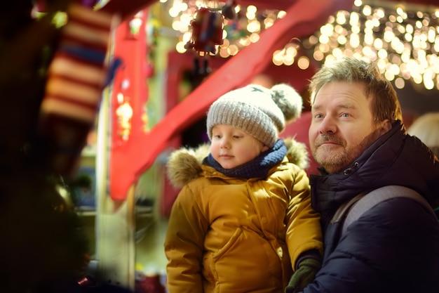 Petit garçon et son père ayant du bon temps sur le marché de noël
