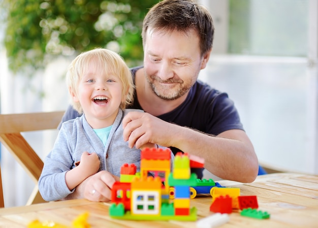 Petit garçon avec son père jouant avec des blocs en plastique colorés à la maison