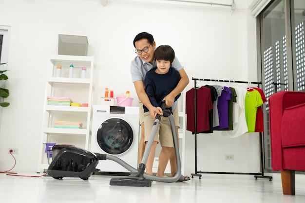 Un petit garçon avec son père passe l'aspirateur dans la pièce. père et fils faisant le ménage dans la maison.