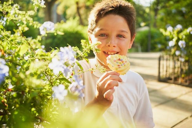 Petit garçon souriant avec des bonbons à côté de fleurs après avoir pleuré
