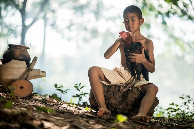 Petit garçon souriant et coq sur la forêt verte dans la campagne