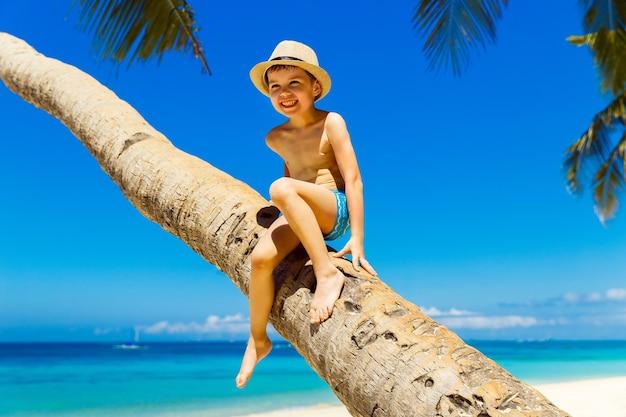 Petit garçon souriant dans un chapeau de paille s'amusant sur un cocotier sur une plage tropicale de sable. le concept de voyage et de vacances en famille.