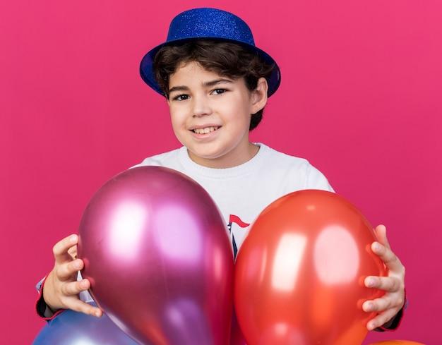 Petit garçon souriant portant un chapeau de fête bleu debout derrière des ballons isolés sur un mur rose