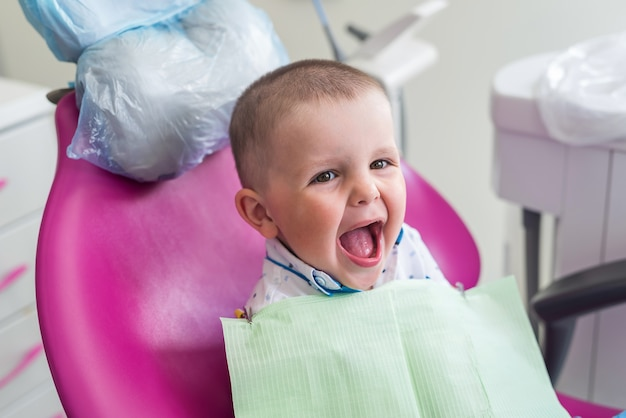 Petit garçon sourit à la chaise du dentiste