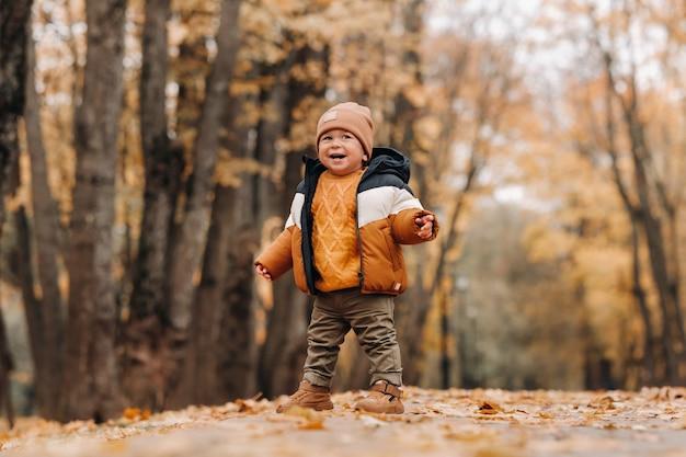 Un petit garçon sourit dans un parc d'automne. une famille se promène dans le parc naturel de l'automne doré.