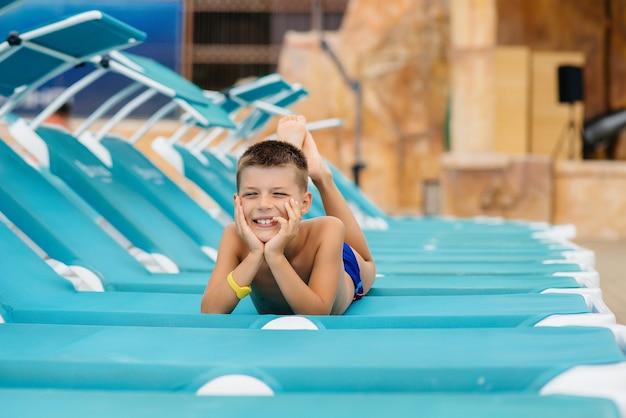 Un petit garçon sourit joyeusement et prend un bain de soleil sur une chaise longue par une journée ensoleillée. bonnes vacances vacances. vacances d'été et tourisme.