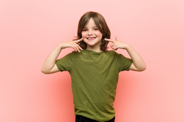 Le petit garçon sourit et pointe ses doigts vers la bouche.