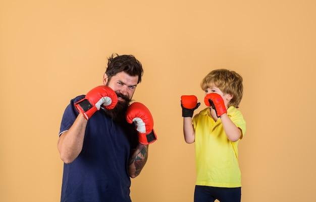 Petit garçon sportif à l'entraînement de boxe avec coach sur ring de boxe homme sportif barbu coaching boxe