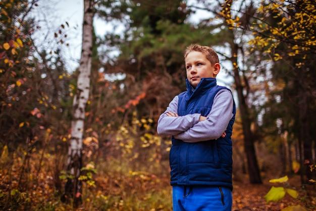Petit garçon sportif se reposant après des exercices en forêt