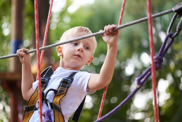 Petit garçon surmonte un obstacle dans un parc d'attractions
