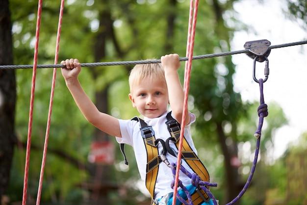Petit garçon surmonte l'obstacle dans le parc à cordes.