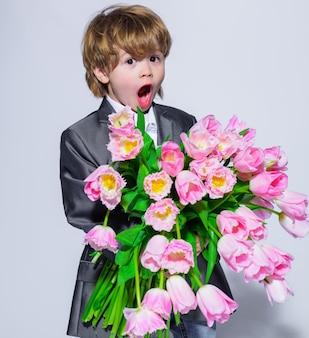 Petit garçon surpris avec bouquet de tulipes. enfant élégant en costume élégant avec des fleurs. anniversaire, fête de la femme, fête des mères, saint valentin.