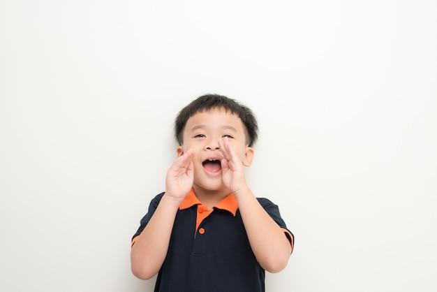 Petit garçon surpris. petit garçon choqué gardant la bouche ouverte et touchant le visage avec les mains en se tenant debout isolé sur blanc