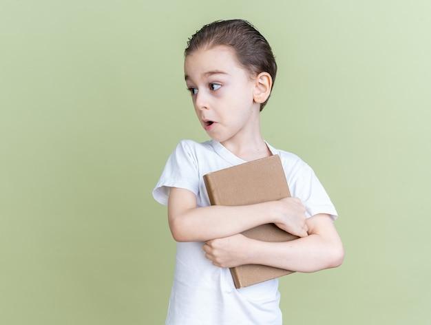 Petit garçon surpris tenant et étreignant le livre en regardant le côté
