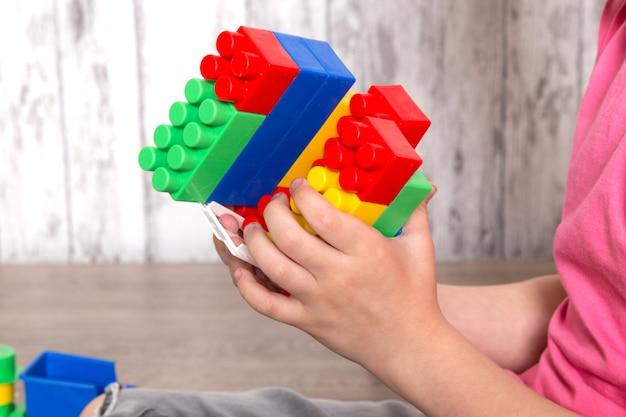 Petit garçon en t-shirt rose et jean gris jouant avec des jouets