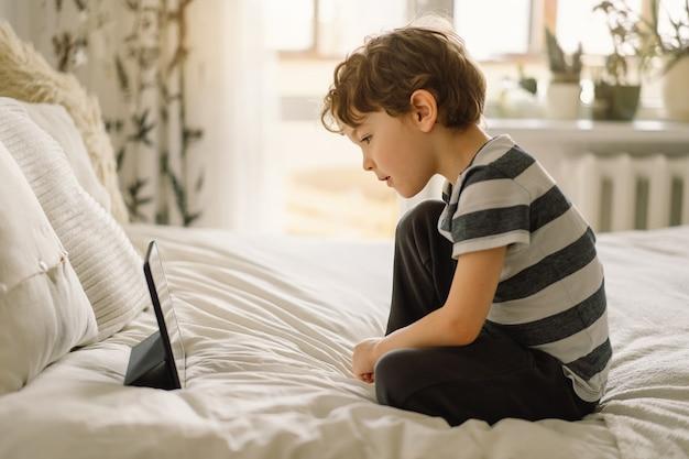 Petit garçon avec une tablette dans la chambre. le garçon joue au jeu sur la tablette. enfant avec un gadget