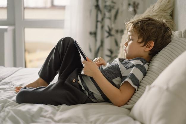 Petit garçon avec une tablette dans la chambre. le garçon joue au jeu sur la tablette