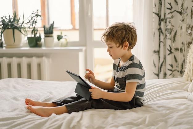 Petit garçon avec une tablette dans la chambre.
