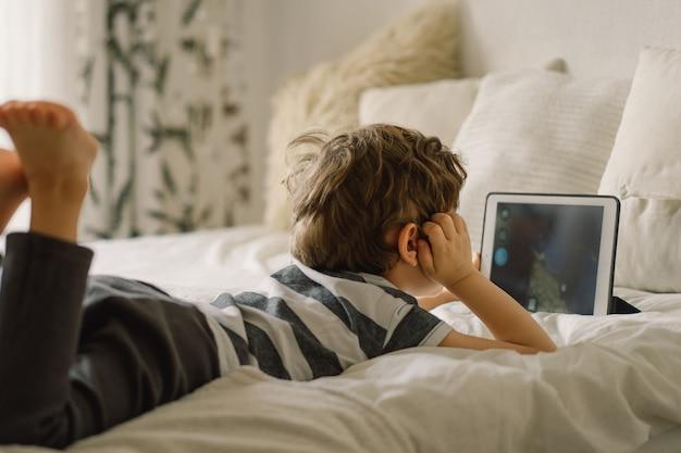 Petit garçon avec une tablette dans la chambre